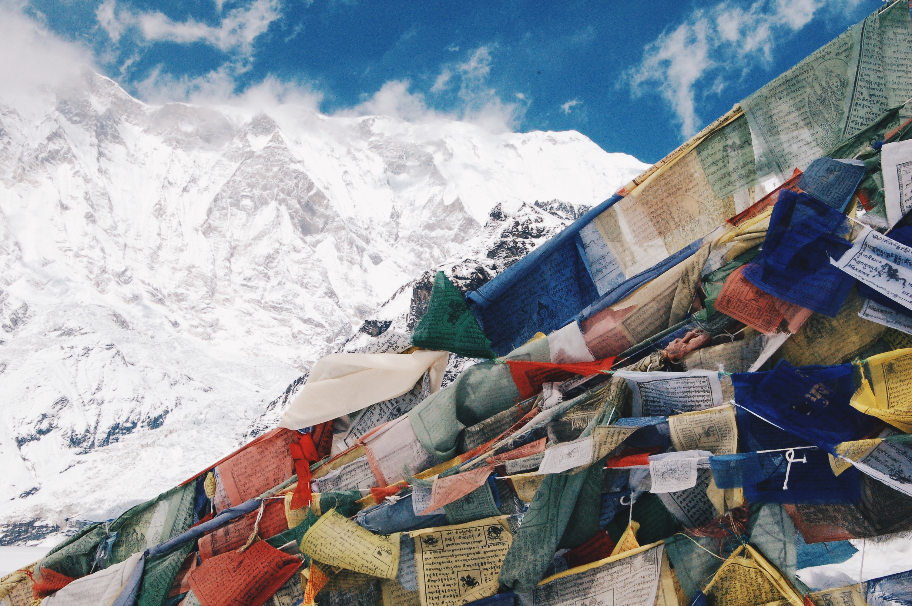 prayer flags in focus with annapurna mountains behind from annapurna base camp