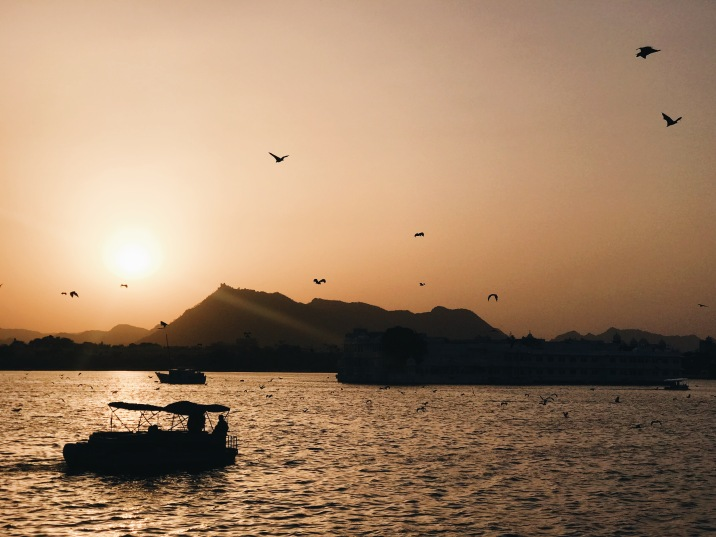 Best Sunset Spot in Udaipur: sunset with boat and bats over water