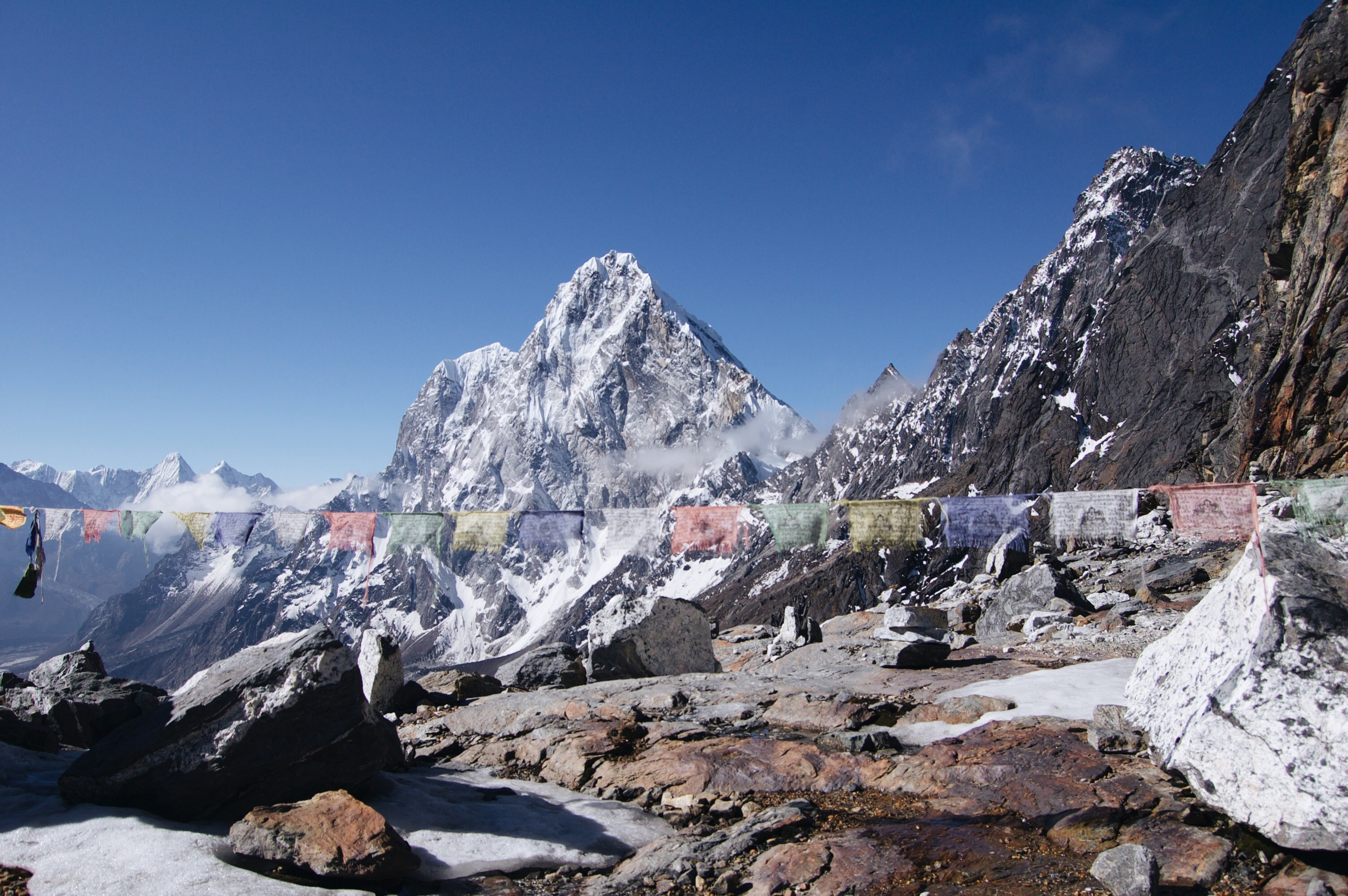 How to Trek the Three Passes Independently: Prayer flags in front of mountains