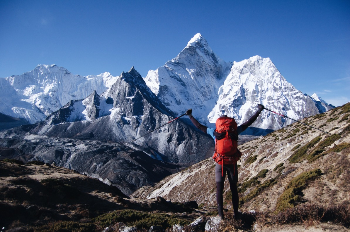 How to Trek the Three Passes Independently: Man with arms up facing away from camera towards mountains