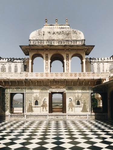 Best Sunset Spot in Udaipur: black and white checkered floor, intricately painted palace walls