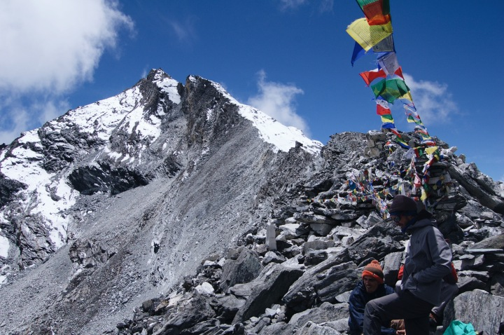 How to Trek the Three Passes Independently: Hiker under prayer flags on a mountain